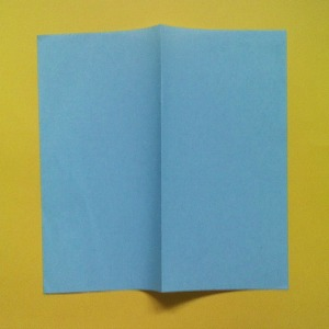 Take a square piece of paper of approximate size 6 inches square.  Make a mountain fold in the center as shown in the photo and make a sharp crease in the paper.